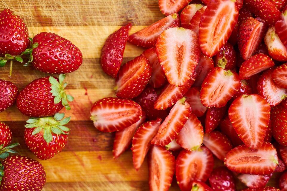 fraises coupées sur une table de cuisine en bois